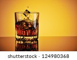 Glass of whisky with ice against yellow background - stock photo