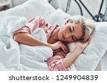 Small photo of Just one more minute in bed. Top view of attractive young woman sleeping while lying in bed at home