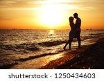 young happy couple on seashore... | Shutterstock . vector #1250434603