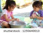 two little girl kneading dough... | Shutterstock . vector #1250640013