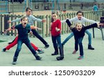 happy russian children showing different figures during game in playground outdoors