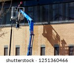 high level window cleaning from telescopic cage or cherry picker. safety cage on boom. high pressure water jet window & exterior washing. worker in red hardhat & in  harness. pressure washing concept  - stock photo