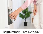 woman filling glass from water... | Shutterstock . vector #1251695539