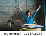Small photo of Happy hipster student rejoicing in success of training project holding hands up.Overjoyed young woman completed studying task during exam preparation sitting at desktop with laptop and textbook