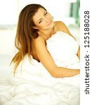 Young woman embracing her pillow in the morning in her bedroom at home - stock photo