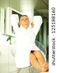 Beautiful brunette woman wearing bathrobe and relaxing at home - stock photo