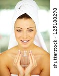 Portrait of a pretty young female wrapped in bath towel and holding a glass of water - stock photo