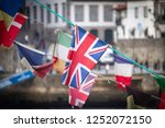 A flag of the United Kingdom waves amidst other national flags (Ireland, France, Denmark), against an old town background.