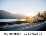 Big rig American white long haul powerful semi truck transporting commercial cargo in bulk semi trailer on straight evening road with scenic sunset in Columbia River Gorge - stock photo