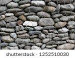 round stones laid in gabion.... | Shutterstock . vector #1252510030