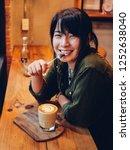 asian woman drinking coffee in  ... | Shutterstock . vector #1252638040