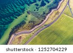 Aerial drone shot of the eastern coastline of Denmark, green grass field with a road on the right and the coastline with clear blue water on de left taken from above, wide birds eye view landscape