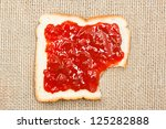 bite out of a slice of bread with strawberry jam on sacking background - stock photo