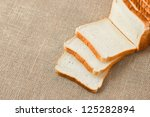 sliced bread on sacking background - stock photo