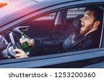 a drunken man driving a car... | Shutterstock . vector #1253200360
