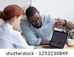 Small photo of Diverse millennial colleagues working together analyzing diagram looking at computer screen. Black mentor helps female apprentice understand corporate program explaining interface showing on monitor