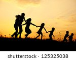 Several happy children running on meadow at summer sunset - stock photo