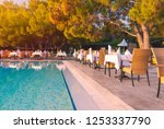 chairs and table near pool at... | Shutterstock . vector #1253337790