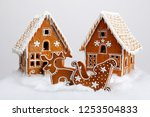 Small photo of The hand-made eatable gingerbread houses, reindeer and cart with snow decoration