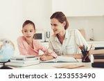 mom helps daughter to do... | Shutterstock . vector #1253553490