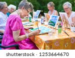Stylish senior lady painting in ...