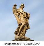 statue of an angel standing on the bridge leading to the Castle Sant'Angelo, Rome - stock photo