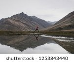 a man jumping over lake with... | Shutterstock . vector #1253843440