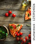 pizza slice on wood with... | Shutterstock . vector #1253924026