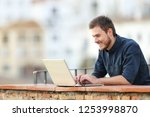 happy man using a laptop in a...   Shutterstock . vector #1253998870