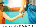 hands of a parent and child in... | Shutterstock . vector #1254342019