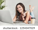 young woman holding credit card ... | Shutterstock . vector #1254347029