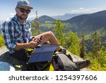 hiker charges its devices using ... | Shutterstock . vector #1254397606
