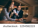 Stock photo woman entrepreneur working on laptop sitting with her colleague in office business partners 1254582223