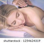 young woman lying on a massage... | Shutterstock . vector #1254624319