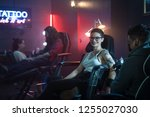Portrait of a pretty short hair teen girl getting a tattoo in arm at beauty parlour. Young millennial gay woman gets body art at night at tattoo studio. Portrait of woman looking at camera