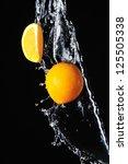 Orange with splash of water on a black background - stock photo