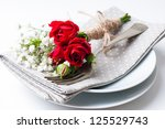 Stock photo festive table setting with red roses napkins and vintage crockery on a white background 125529743