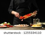 chef pours cherry tomatoes in a ... | Shutterstock . vector #1255334110