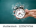 hand holds clock time minute... | Shutterstock . vector #1255674766