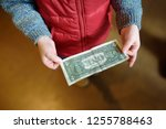little boy holds a one dollar... | Shutterstock . vector #1255788463