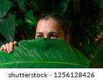 girl hiding among tropical...   Shutterstock . vector #1256128426