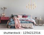 Stock photo flowers in stylish glass vase on diy velvet covered pastel pink and burgundy nightstand next to 1256212516