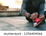 close up of a fitness man tying ... | Shutterstock . vector #1256404066