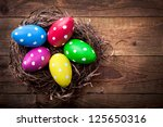 Colorful easter eggs with white points in straw nest on a wooden table