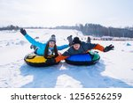friends having fun. snow tubing.... | Shutterstock . vector #1256526259