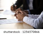 Small photo of Lawyer solicitor with clasped hands consulting client about document making financial legal deal sell law services, close up view of business counselor or agreement party at contract signing concept
