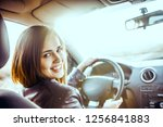 woman in car indoor keeps wheel ... | Shutterstock . vector #1256841883