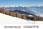 Snow covered alpine mountain peaks tower above a steep ski run in South Tyrol, Italy. - stock photo