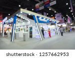 Small photo of Blur background of people in electronic fair expo at big exhibition hall event trade show room. Meetings, incentives, conferences and exhibitions (MICE) business and commercial trading concept.