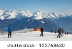 Skiers on a ski run in the Dolomites, South Tyrol, on a beautiful winter day. - stock photo